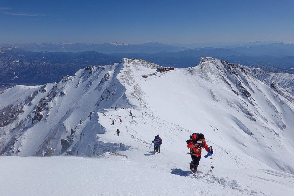 積雪期・唐松岳・下山開始、前には唐松岳頂上山荘。さらに後ろには浅間山や四阿山が