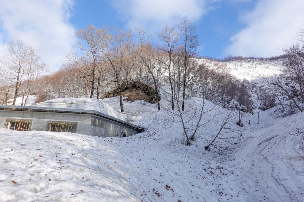 残雪期・日向倉山・コチラの建物の右側から登頂スタート