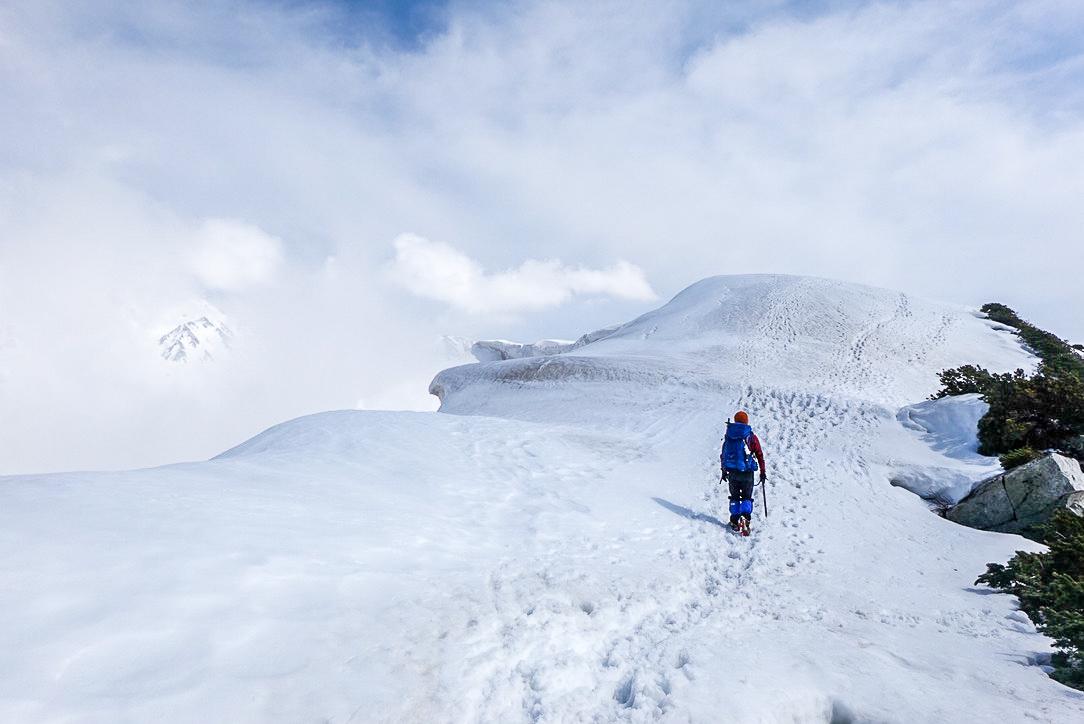 残雪期・奥大日岳・雲の間から剱岳